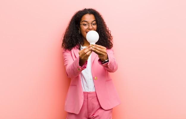 Giovane donna graziosa nera con una lampadina che ha un'idea contro il muro rosa