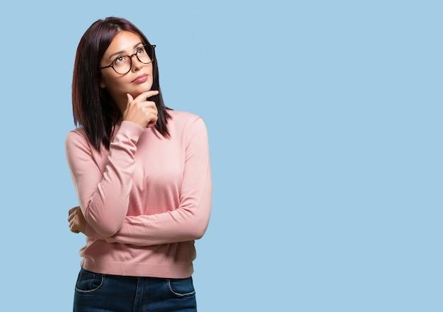 Giovane donna graziosa pensando e alzando lo sguardo, confuso su un'idea
