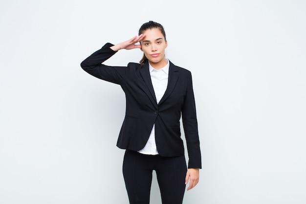 Giovane donna graziosa saluto con un saluto militare in un atto di onore e patriottismo, mostrando rispetto concetto di business