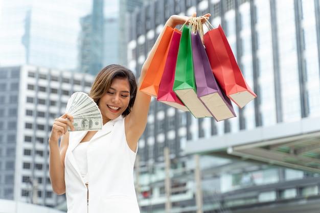 Giovane donna graziosa soddisfatta dei sacchetti della spesa