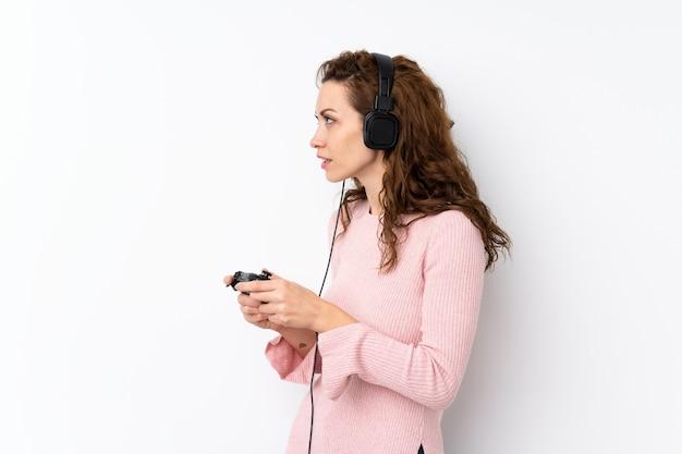 Giovane donna graziosa sopra isolata giocando ai videogiochi