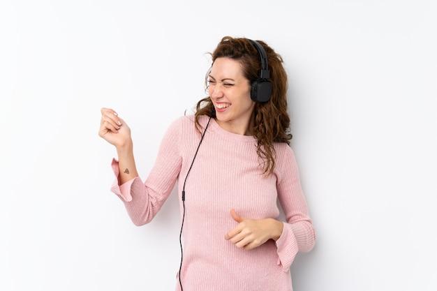 Giovane donna graziosa sopra isolata usando il cellulare con le cuffie e ballare