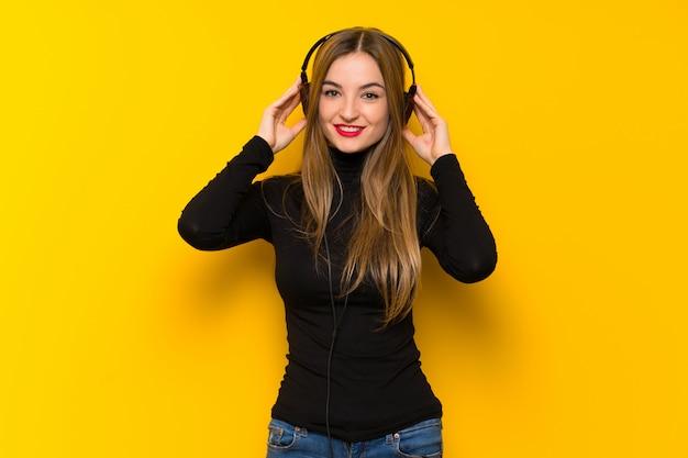 Giovane donna graziosa sopra la parete gialla che ascolta la musica con le cuffie