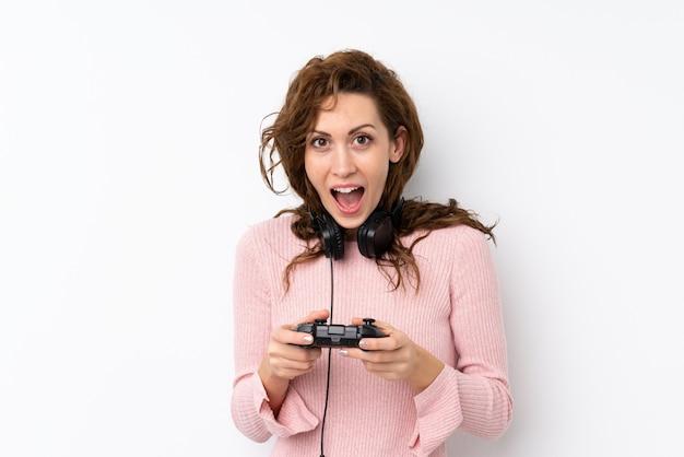 Giovane donna graziosa sopra la parete isolata che gioca ai videogiochi