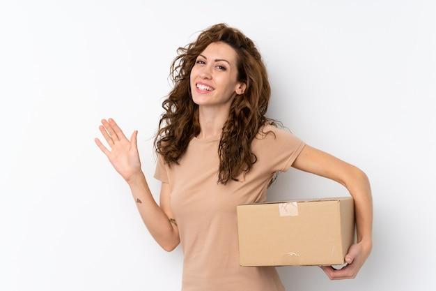 Giovane donna graziosa sopra la parete isolata che tiene una scatola per spostarla in un altro sito e salutare