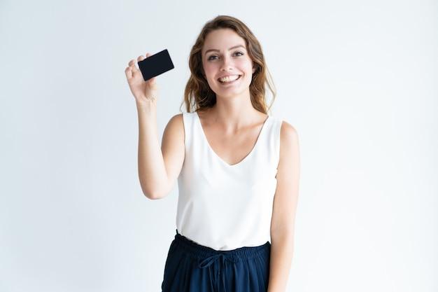Giovane donna graziosa sorridente che mostra carta di plastica in bianco
