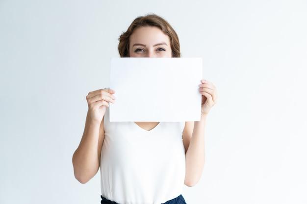 Giovane donna graziosa sorridente che si nasconde dietro il foglio di carta in bianco