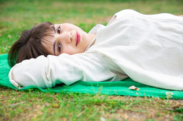 Giovane donna graziosa sorridente che si trova e che si rilassa sul prato inglese