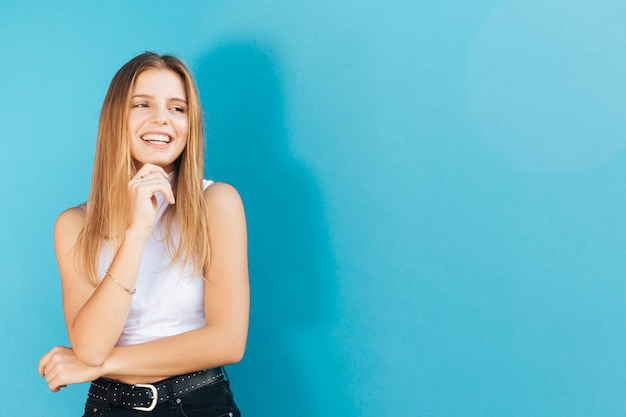 Giovane donna graziosa sorridente con la sua mano sul mento che esamina macchina fotografica contro la parete blu