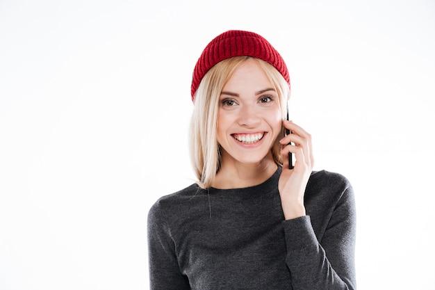 Giovane donna graziosa sorridente in cappello che parla sul telefono cellulare