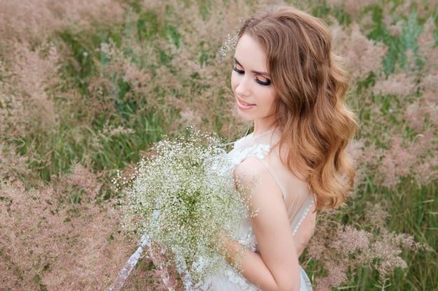 Giovane donna graziosa (sposa) in abito da sposa bianco all'aperto, acconciatura