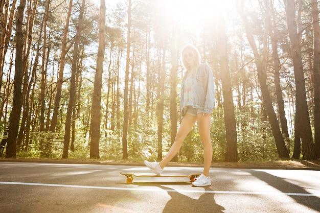 Giovane donna graziosa su skateboard all'aperto