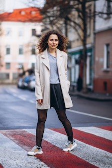 Giovane donna graziosa su un attraversamento pedonale