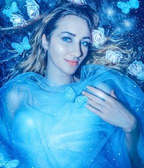 Giovane donna graziosa sul fondo misterioso della foresta con le farfalle blu e la fine magica della luce su