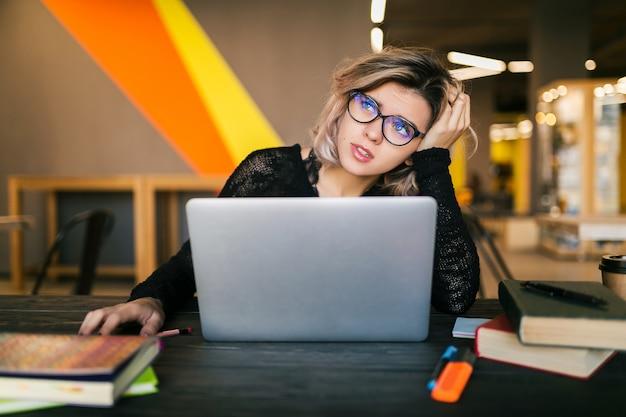 Giovane donna graziosa triste stanca che si siede al tavolo che lavora al computer portatile nell'ufficio di co-working, con gli occhiali, stress sul lavoro, emozione divertente, studente in aula, frustrazione