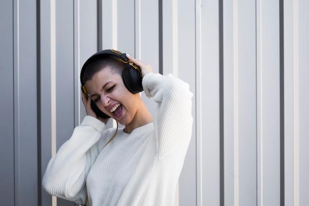 Giovane donna grimacing con i capelli corti che ascolta la musica in cuffia
