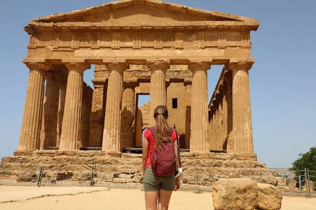 Giovane donna guarda al tempio della concordia nella valle dei templi agrigento, sicilia. ragazza viaggiatore visita i templi greci nel sud italia.