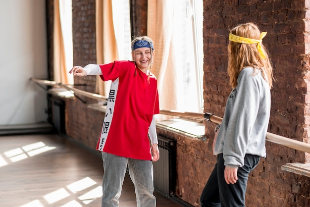 Giovane donna guardando la sua amica ballando in classe