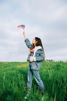 Giovane donna guardando piccola bandiera americana in braccio