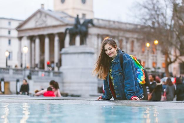 Giovane donna guardando se stessa in una fontana a londra
