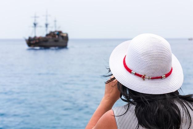 Giovane donna guardando una barca con il binocolo