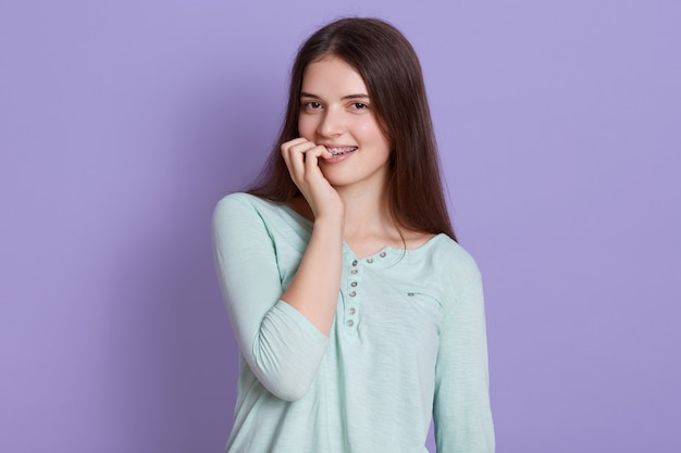 Giovane donna hared scura che porta camicia casuale che esamina macchina fotografica e che morde le sue dita