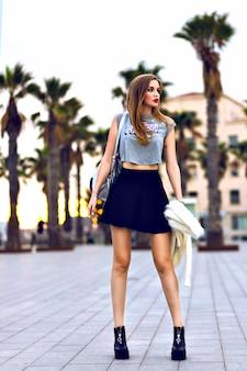 Giovane donna hipster in posa sulla spiaggia della california al tramonto, soleggiato periodo autunnale, indossando giacca di pelliccia sintetica alla moda e minigonna