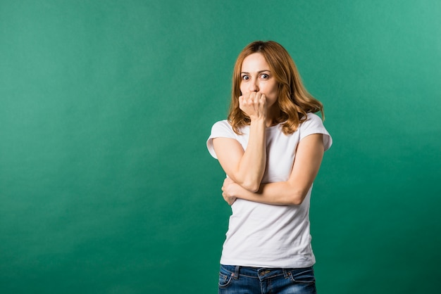 Giovane donna impaurita che copre la sua bocca contro il contesto verde