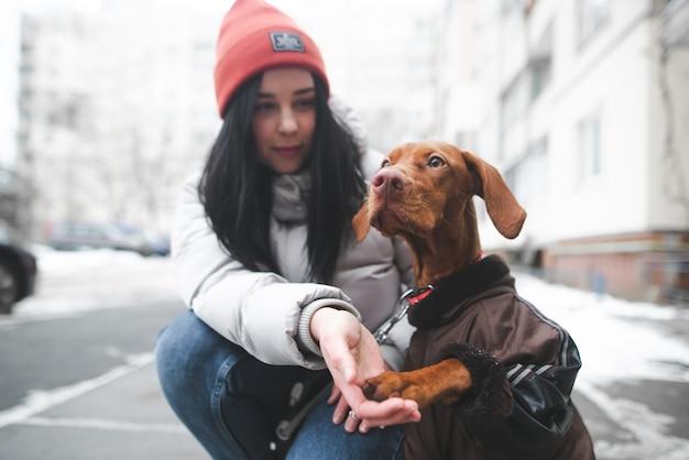Giovane donna in abiti caldi si siede a terra con un cucciolo