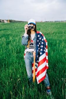 Giovane donna in abiti jeans e cappello colorato utilizzando dispositivo vintage