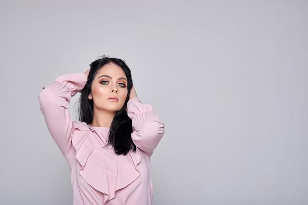 Giovane donna in abiti rosa. ragazza che posa su una parete grigia.