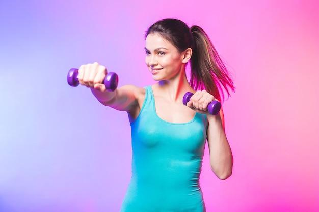 Giovane donna in abiti sportivi con un bel sorriso che tiene il manubrio del peso facendo allenamento fitness