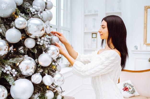 Giovane donna in abito accanto all'albero di natale