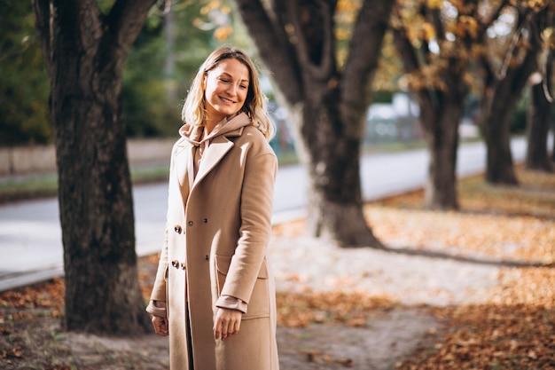 Giovane donna in abito beige fuori in un parco in autunno