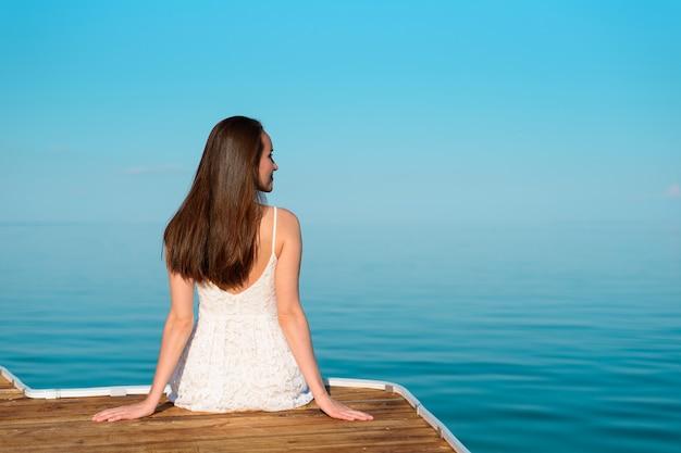 Giovane donna in abito bianco seduto su un molo di legno guardando lontano, contro il mare blu