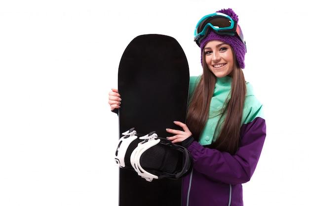 Giovane donna in abito da sci viola tenere snowboard