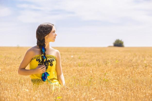 Giovane donna in abito giallo nel campo di grano