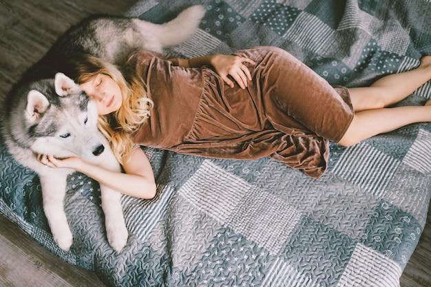 Giovane donna in abito marrone sdraiato sul cucciolo di husky sul letto.