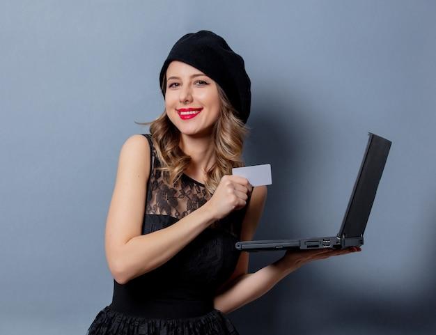 Giovane donna in abito nero con notebook e carta sul muro grigio