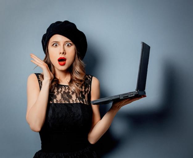 Giovane donna in abito nero con notebook sulla parete grigia