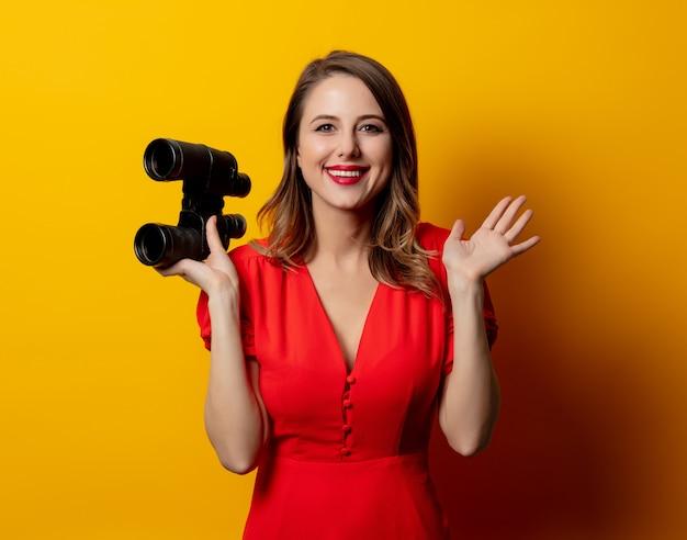 Giovane donna in abito rosso con binocolo sulla parete gialla