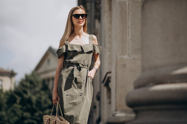 Giovane donna in abito verde in piedi dal vecchio edificio
