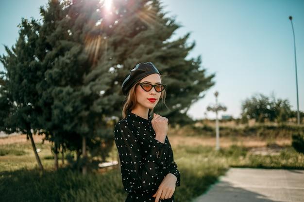 Giovane donna in abito vintage nero a pois in posa all'esterno
