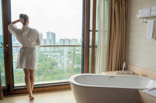 Giovane donna in accappatoio bianco in bagno di lusso con vista sulla città