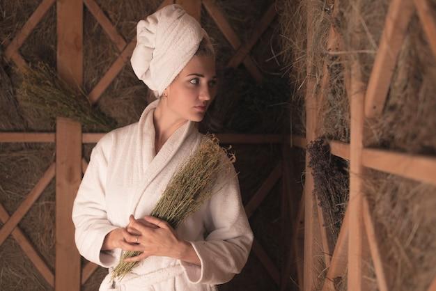 Giovane donna in accappatoio che tiene le erbe mediche
