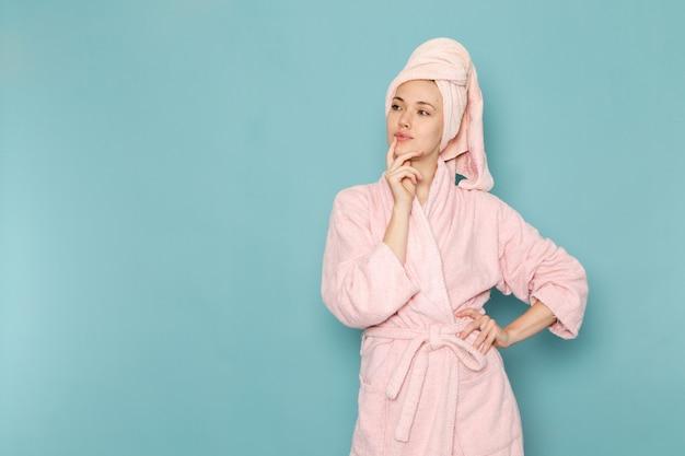 Giovane donna in accappatoio rosa dopo la doccia in posa e pensando sul blu