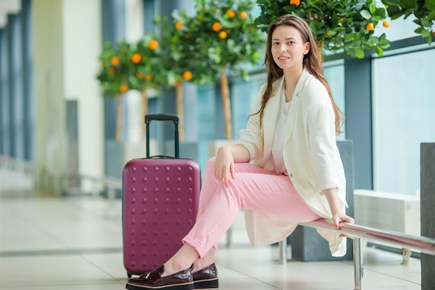 Giovane donna in aeroporto internazionale con i suoi bagagli e caffè per andare in attesa del suo volo