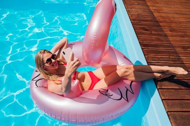 Giovane donna in anello di nuotata prendendo un selfie
