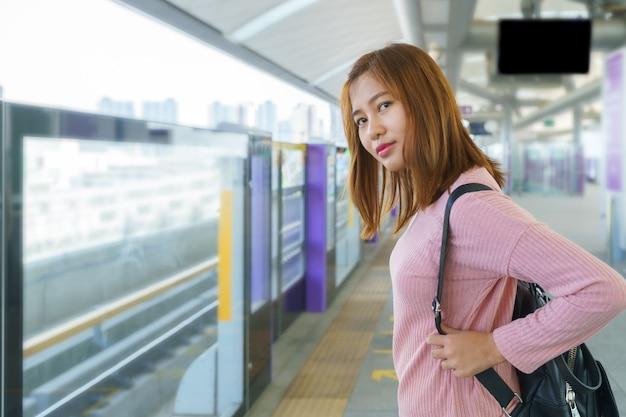 Giovane donna in attesa e in cerca di sky train in piattaforma