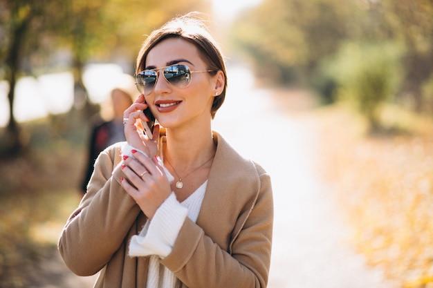 Giovane donna in autunno parco utilizzando il telefono